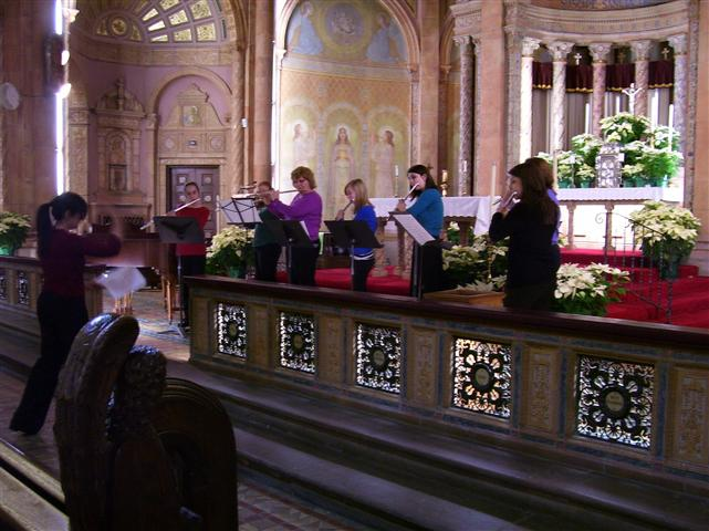 "A verse from today's Gospel (Mt. 15:26) is repeated in the ceramic medallions on the church altar rail, pictured here in a photo of the Buffalo Flute Club in recital at Blessed Trinity. The Latin words ""Vere Panis Filiorum Non Mittendus Canibus"" are taken from Christ's exchange with a Canaanite woman who seeks healing for her daughter. When the church was built, the Eucharist was offered to the people kneeling at the rail. While Christ used these words to test the woman's faith, ""they are applied here in the sense of never to deprive anyone...of the blessings of the Eucharist...."" Rev. Walter Kern's ""Guidebook to Blessed Trinity R.C. Church,"" pp. 31-32."