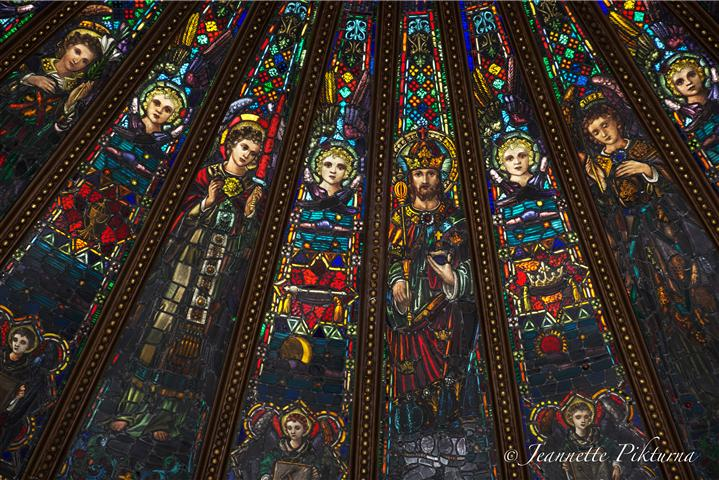 "Detail of church's stained glass skylight, the theme of which is Christ the King. ""The central panel shows Christ reigning as Lord of the kingdom that we pray will come."" Surrounding panels contain figures of angels and symbols both of Christ's suffering and His glorification. Photo credit: Jeannette Pikturna."