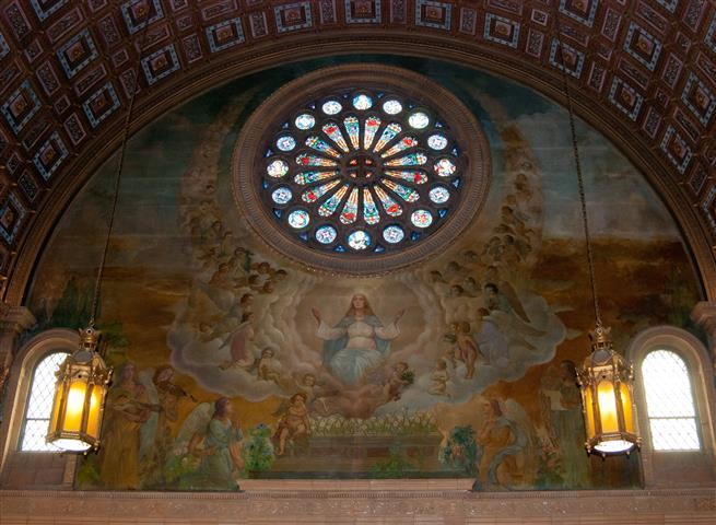 """Much of the left (east) transept wall of Blessed Trinity Church is covered by this large painting of the Assumption of Mary into Heaven by Joseph Mazur. The theme of the artist's rendering """"is the crowning of [the] good life of Mary with heavenly joy; … the goal of every Christian's life.""""  (Rev. Walter Kern's Guidebook to Blessed Trinity R. C. Church, p. 45). Photo credit: Steve Mangione."""