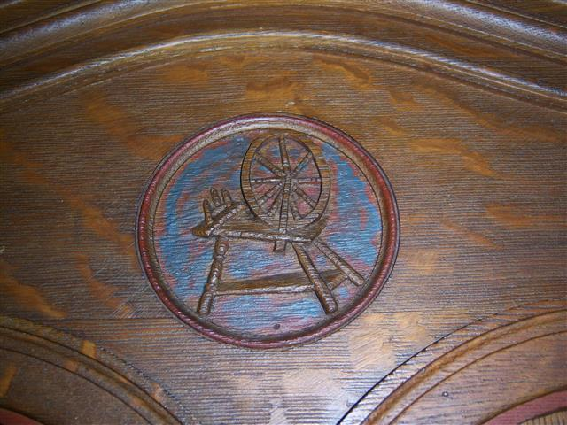 The weaver or textile worker is represented by the spinning wheel.