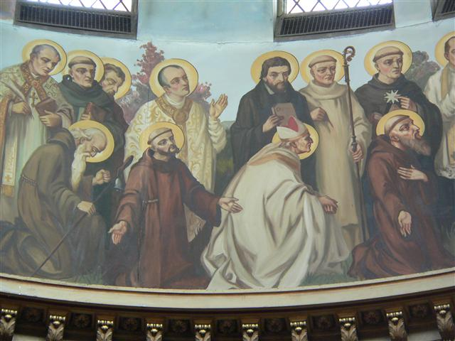 "St. Ignatius of Loyola (1491-1556) and St. Alphonsus Liguori (1695-1787), whose feast days we celebrate this week, are both depicted in a in a group of twelve figures identified as ""Monks, Hermits, and Religious"" in the dome of our church. St. Ignatius, fourth from the left (standing), was on his way to military fame before a debilitating war injury. His conversion experience began during his convalescence, and his writings during that time culminated in his greatest work, the Spiritual Exercises. Founder of the Jesuits, his feastday is July 31. St. Alphonsus, the first standing figure on the left, is pictured with a pen and book. Although he acquired fame as a writer, the founder of the Redemptorist Congregation is also remembered for his preaching and pastoral reforms. His feast is celebrated on August 1. The dome painting is by Buffalo-born artist Joseph Mazur; the photo by Gary Kelley."