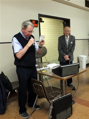 Jerry Powers, '51, reads the names of the split club raffle winners as Clate Steinwachs, '30, who drew the winning tickets, looks on. (Mr. Steinwachs celebrated his 99th birthday on September 3rd).