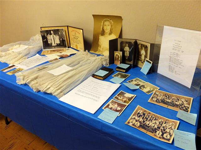 Marilyn Gesl Arcara, '45, prepared a display showing the history of 5 generations of the Gesl Family at Blessed Trinity. The display included her First Communion photo and the dress she wore.