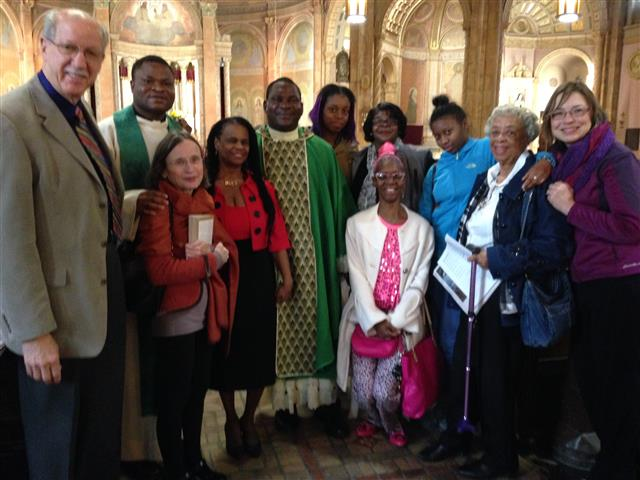 Father Victor Ibhawa (center) is welcomed by parishioners following Sunday Mass on November 6.